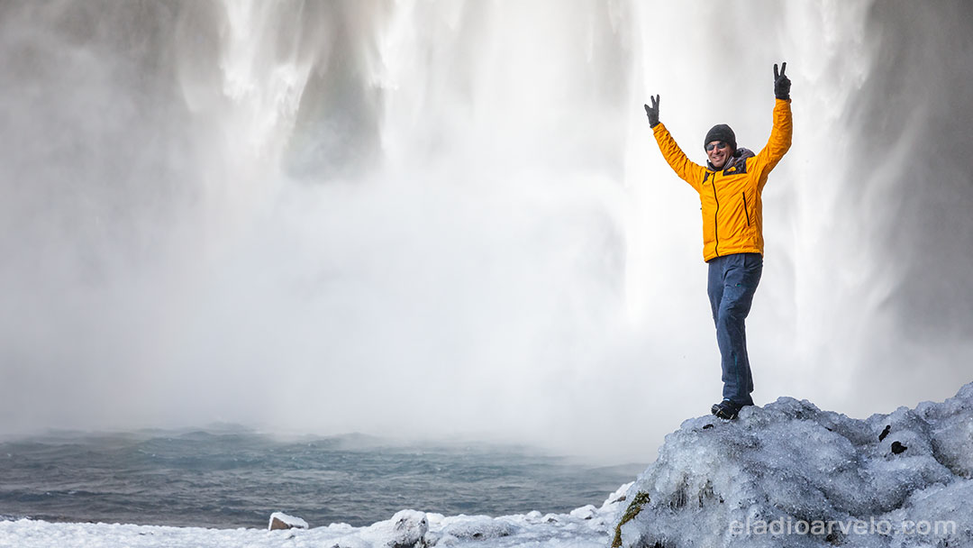 Standing on ice by the water's edge at Skogafoss.