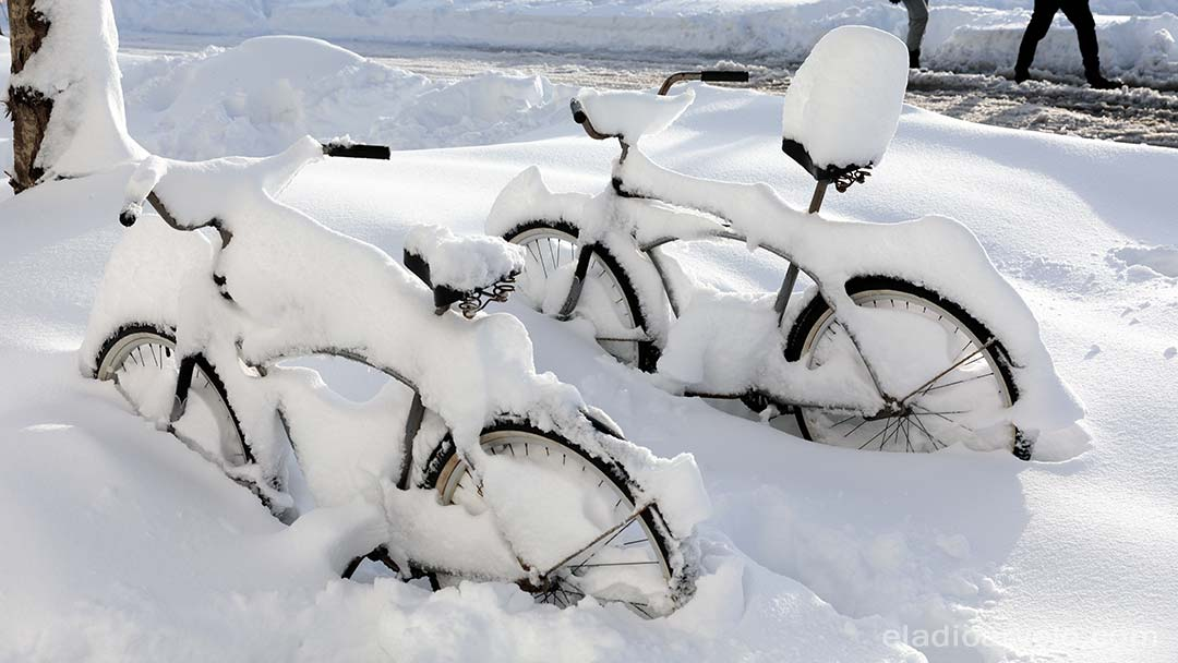 Bicycles covered in snow.