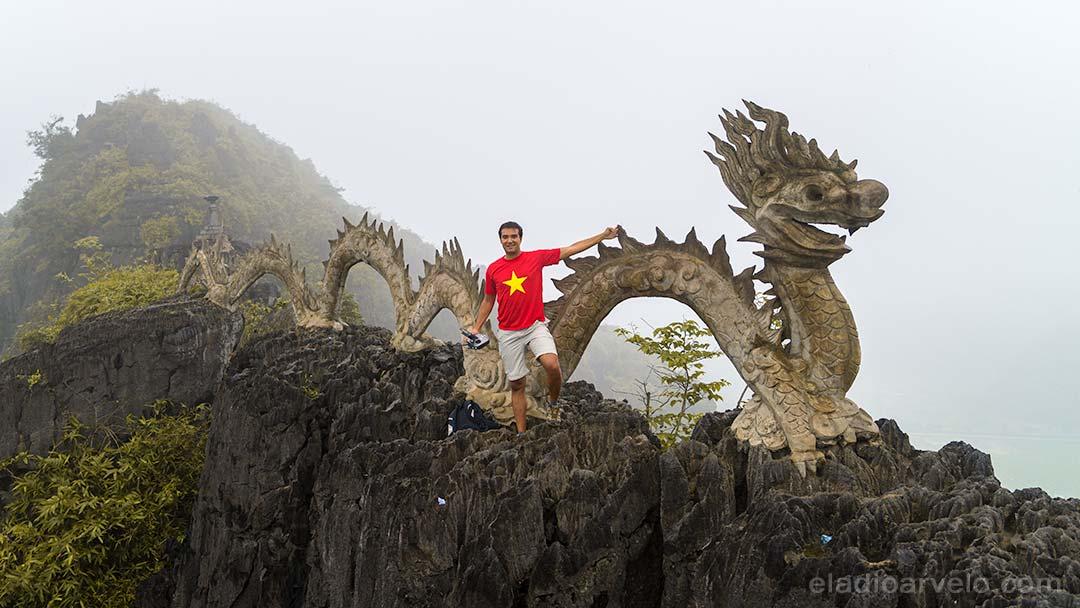 Eladio standing next to the stone carved dragon atop Hang Mua Peak in Ninh Binh.